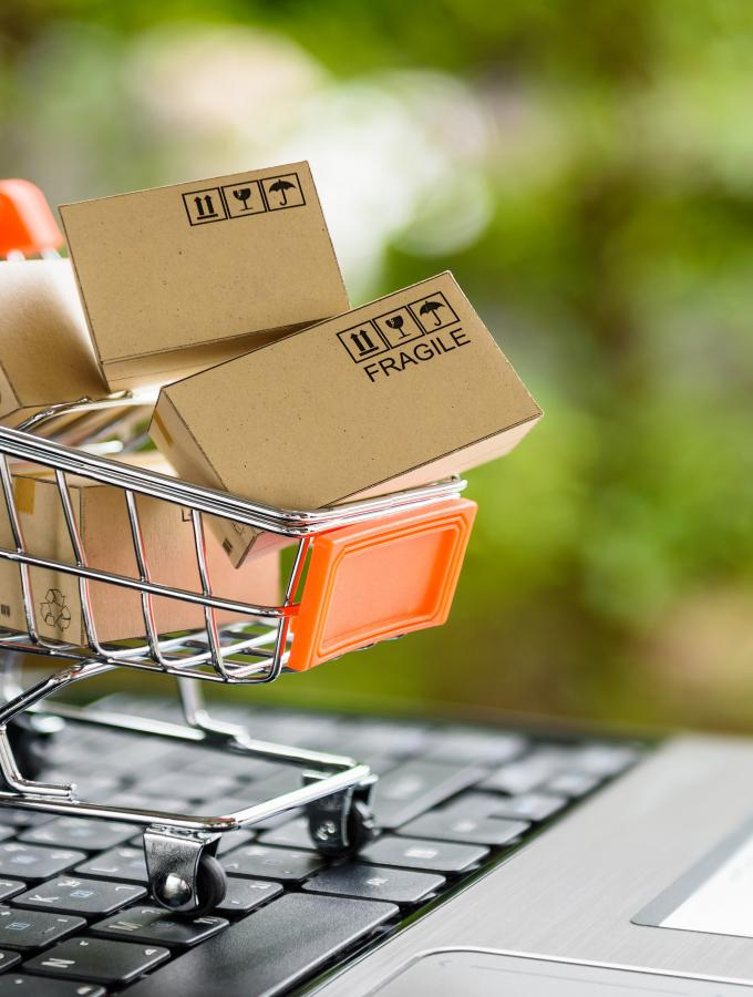 Miniature scale shopping cart with shipping boxes in it on top of a laptop keyboard