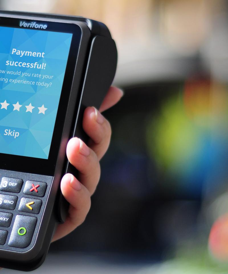 Verifone V400m portable payment device held in hand with blurred outdoor background