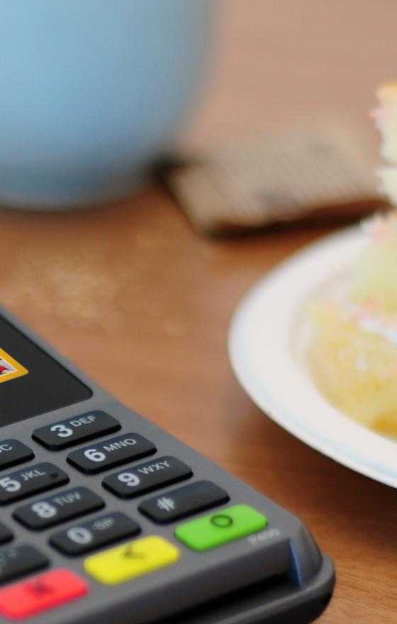 Verifone's P400 PIN pad on a table next to a cup of coffee and a slice of strawberry shortcake